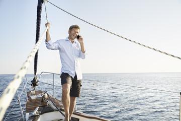 "Mediterranean Sea, ""Goldene Rente"", laughing mature man using smart phone on sailing boat"