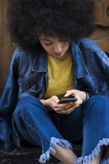 Young woman wearing jeans and jeans jacket using cell phone