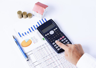 Calculator and financial chart with pen and coins and house paper for Loan concept