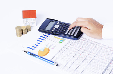 Calculator and pen on business chart with coins stack and house paper for home loan concept
