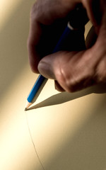 Human's hand holding pencil to write on the paper in shadow
