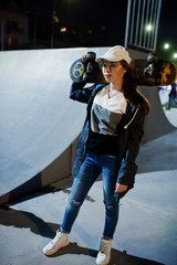 Young teenage urban girl with skateboard, wear on glasses, cap and ripped jeans at skate park on the evening.