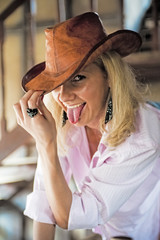 The girl in the cowboy hat fool around, showing the tongue.