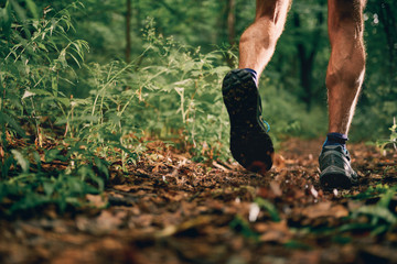 Muscular calves of a fit male jogger training for cross country forest trail race in nature park.