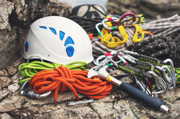 Used climbing equipment - carabiner without scratches, climbing hammer, white helmet and grey,red,green and black rope