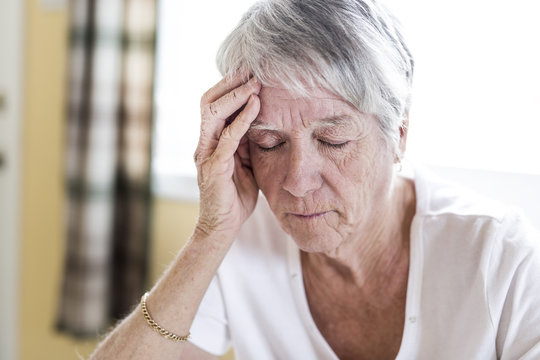Mature woman at home touching her head with her hands while having a headache pain