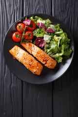 Glazed salmon fillet and fresh vegetable salad close-up on the table. Vertical top view