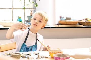 Fototapeta Ceramika dla dzieci. Dzieci lepią z gliny w pracowni ceramiki artystycznej  obraz