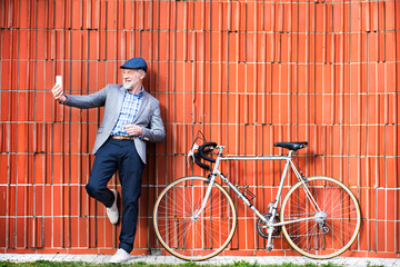 Senior man with smartphone and bicycle against brick wall.