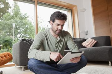 Germany, Bavaria, Nuremberg, Mature man using digital tablet in living room