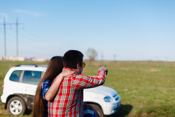 Young couple travels to plaid shirts and shorts and the dog sitting on the grass back near the car and admire the scenery. Tourists rest on the hill opposite the grass field staring at the horizon.