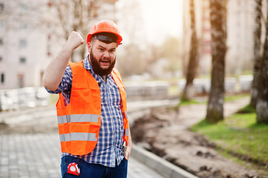 Portrait of brutal angry beard worker man suit construction worker in safety orange helmet against pavement with showing arms.
