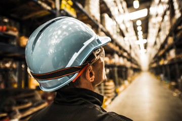 Modern Warehouse Worker in Safety Helmet and Goggles