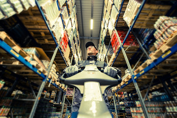 Caucasian Worker in uniform with pallet jack looking for package