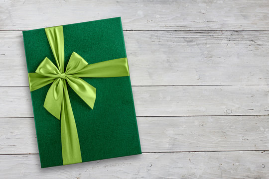 Green gift box over wood background with copy space, top view