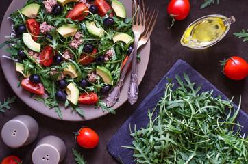 Salad with avocado arugula tomato olives tuna with lemon dressing