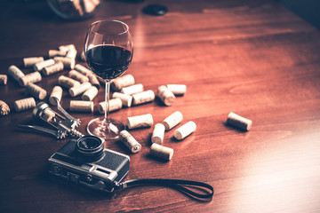 Retro camera and wine on wood table background. Vintage concept.