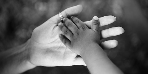 Child's hand in the hand of an adult. Black and white photo about the trust and joy of parenting and childhood