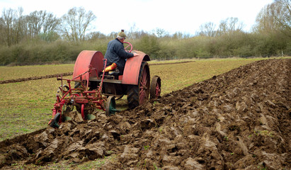 Vintage red International 1930's  tractor ploughing field.