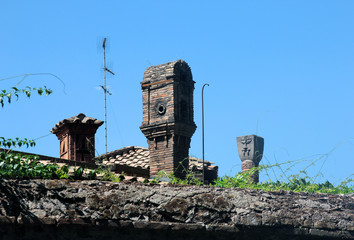 beautiful vintage Italian medieval red brick chimneys on blue sky background