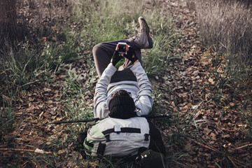 Man backpacker lying on the mountain using a mobile