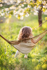 Pretty child girl is having fun in hammock outdoors