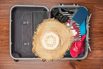 Open travel bag with clothes and accessories closeup