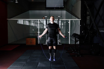 Muscle man skipping rope. Athlete using jump ropes for the workout in a cross-training gym. Man jumping rope at the gym