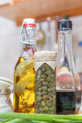 Caper in glass jar, balsamic vinegar and olive oil with pepper and spices in glass bottles in a modern kitchen. Shallow depth of field. Toned.