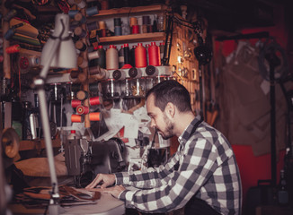 Adult man worker working on stitches for belt