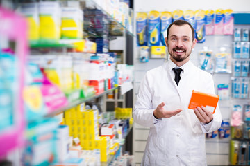 Cheerful male pharmacist suggesting useful drug