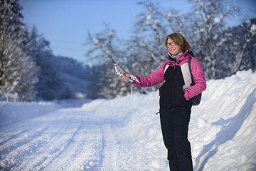 Girl with mobile phone doing selfie on snow