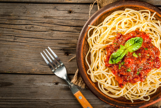 Italian cuisine. Lunch or dinner. A serving of spaghetti pasta with tomato marinara sauce and basil on a dark wooden table. Copy space top view