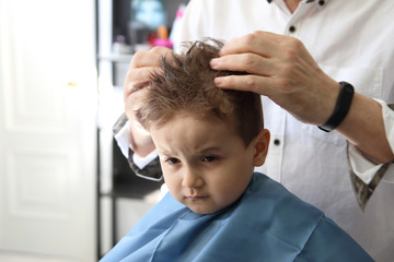 peluquero poniendo gomina a niño pequeño en la peluquería
