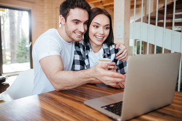 hugging couple near laptop