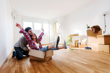 Happy young couple moving in new home unpacking boxes Wall mural