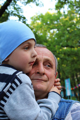 Grandfather holds a small grandson in his arms. Both look to the side.