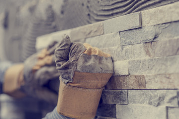 Toned image of hands of tiler worker in gloves