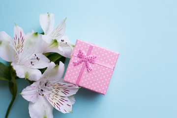Pink gift box with alstroemeria flowers on light blue background