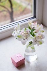 Beautiful tender bouquet of Alstroemeria with pink gift box near window