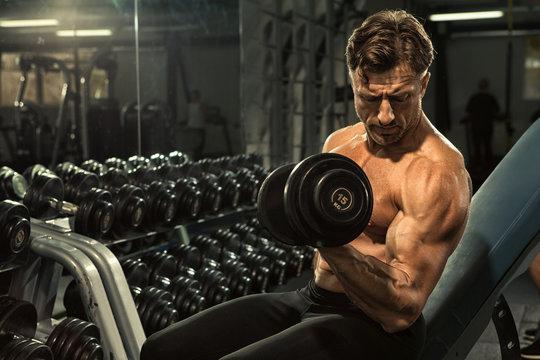 Mature shirtless bodybuilder man pumping iron at the gym