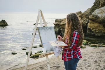 Female artist painting a sea landscape
