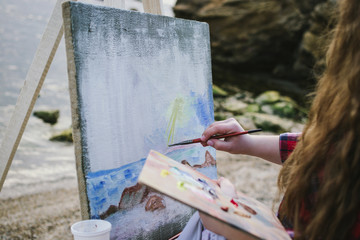 Female artist painting a sea landscape close up