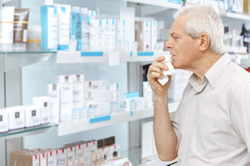 Sick elderly customer choosing medications at the pharmacy