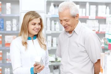 Young female pharmacist helping an elderly customer