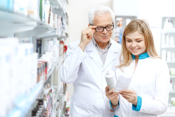 Elderly pharmacist and his young colleague working at the drugstore together