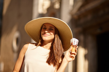 Beautiful young brunette woman having refreshing ice cream - Small depth of field
