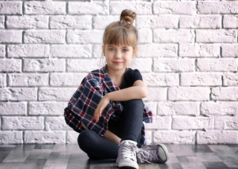 Cute stylish girl sitting on floor near light brick wall