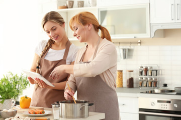 Young woman and her mother cooking in kitchen
