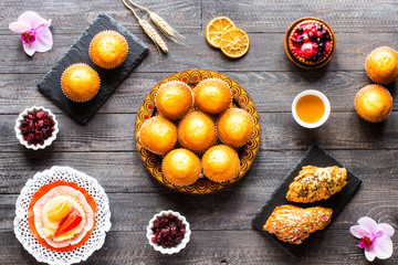 Delicious homemade muffins with yogurt, on a wooden background with space for text.